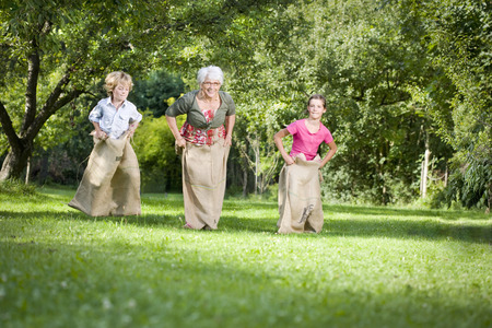 bounding: Children sack racing with grandmother