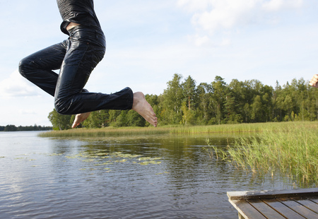 Man jumping in the lake with his clothes