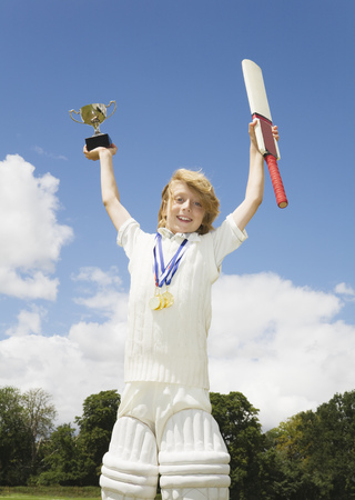 Boy with Cricket Bat, medals and Trophy LANG_EVOIMAGES
