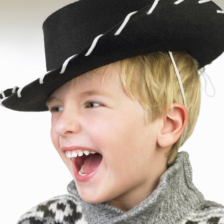 niños vistiendose: Niño con un sombrero de vaquero, sonriendo