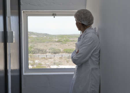 corridors: Factory worker looking out of window