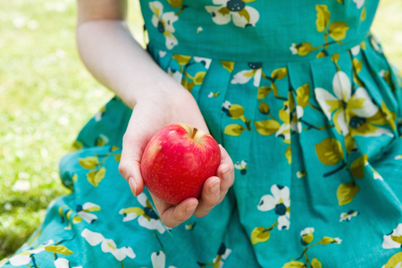 tempted: Womans hand holding apple.