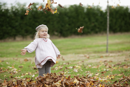 tosses: Little girl throwing leaves in the air