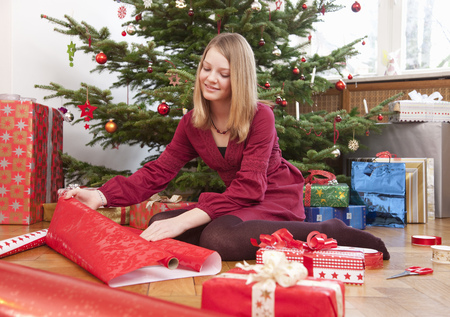 customs and celebrations: girl wrapping christmas presents LANG_EVOIMAGES