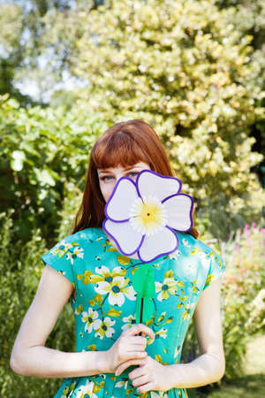 bashfulness: woman peeping from behind fabric flower. LANG_EVOIMAGES