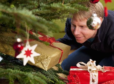 man hiding presents under christmas tree