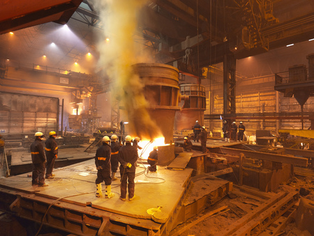 Steel Workers In Plant Working On Ladle