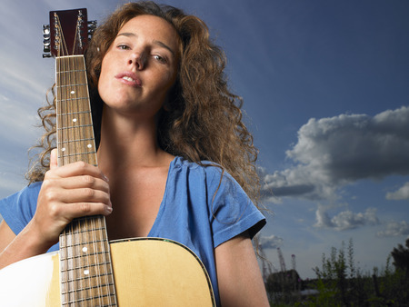 Woman holding her guitar LANG_EVOIMAGES