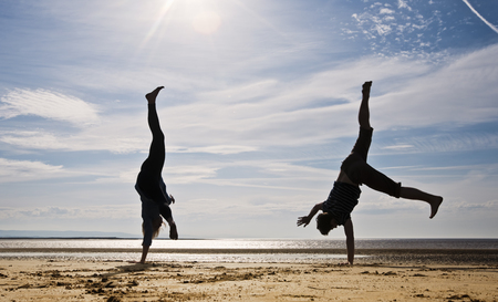 low spirited: Two people cartwheeling on beach