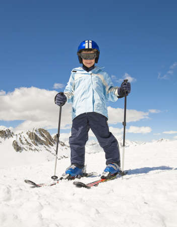 ceasing: Boy skiing in snow,mountain backdrop