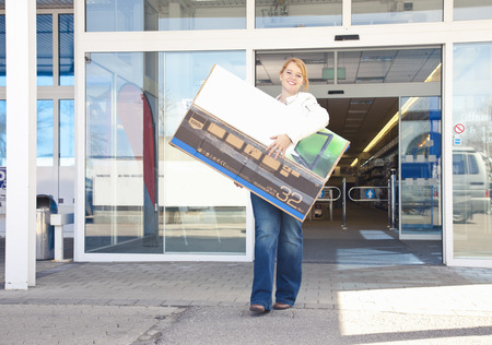 stockmarket: Girl carrying new-bought TV out of store LANG_EVOIMAGES