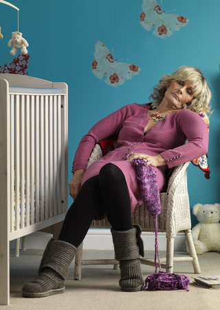 retiring: Mature woman asleep in chair next to cot