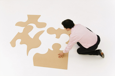 four objects: Business man looks to finish puzzle