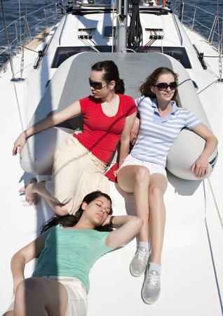 Three girls sitting on yacht