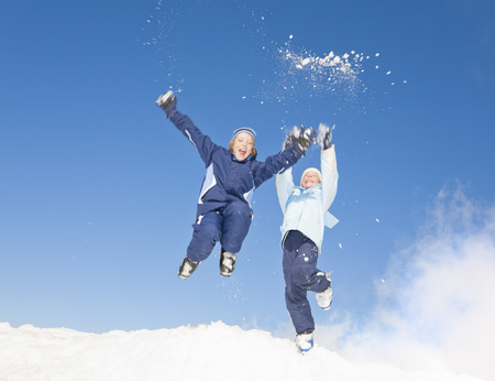 Boys (8-11) jumping in snow LANG_EVOIMAGES