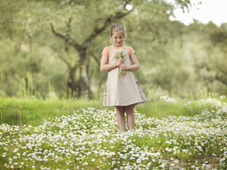 Child holding a bunch of daisies