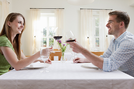passions: Couple at restaurant toasting with wine