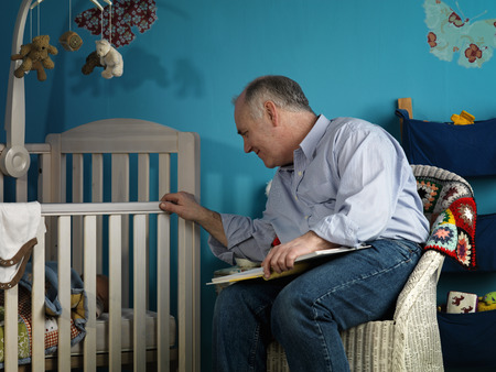 sooth: Mature male sitting with baby in cot