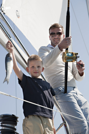 Father and son fishing on yacht LANG_EVOIMAGES