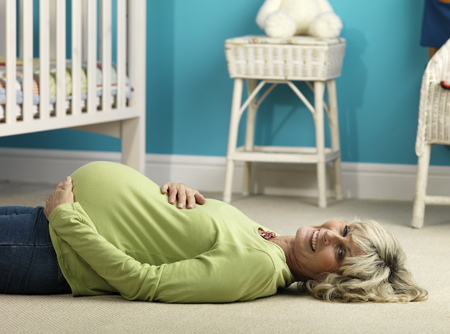 jeopardizing: Pregnant older woman lying on floor LANG_EVOIMAGES