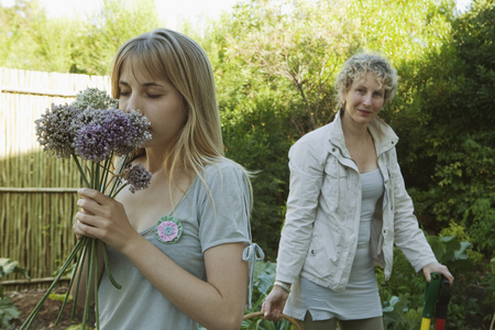assembled: Young woman smelling flowers in garden