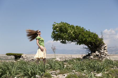 Woman with windblown hair and tree LANG_EVOIMAGES