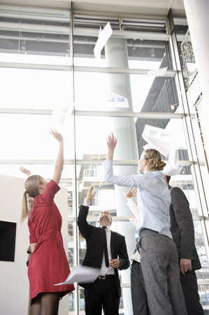 low spirited: Business team throwing papers in the air LANG_EVOIMAGES