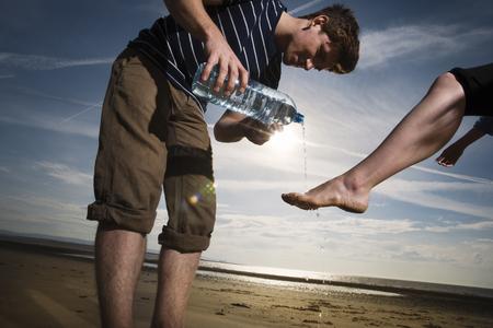 help section: Man washing womans feet on beach