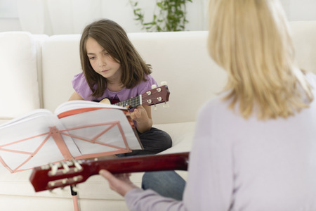 Girl having a lesson on the guitar
