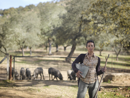 omnivore: Woman on farm holding bucket and stick
