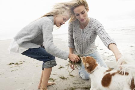 agachado: Familia joven en la playa en otoño