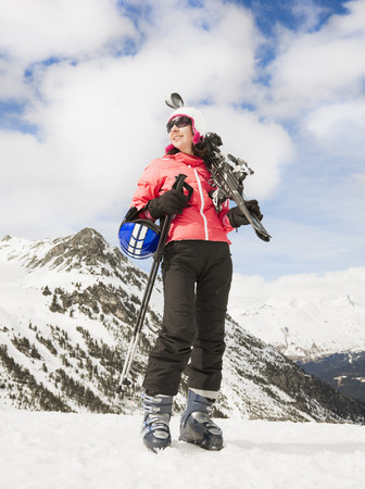 mountainous: Woman with skis in snowy mountains