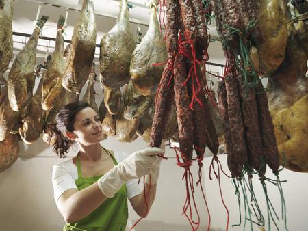 chorizos: Woman looking at hanging chorizos LANG_EVOIMAGES