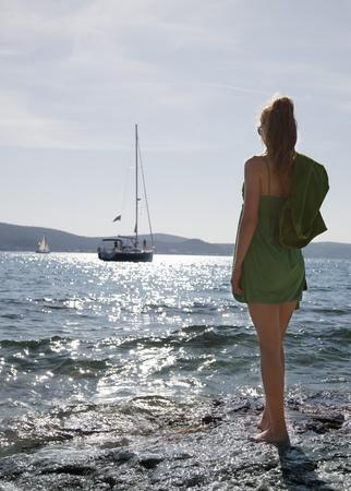 summers: Woman at beach looking at yacht