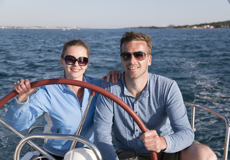 truelove: Man and woman steering yacht