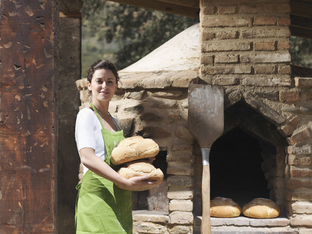antiquity: Woman holding freshly made bread loaves
