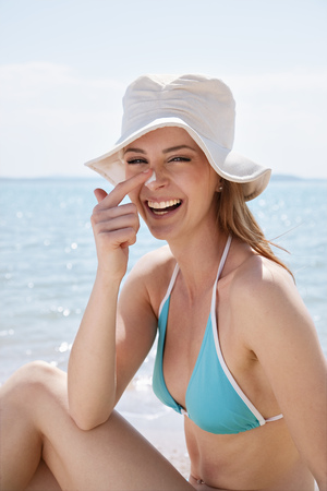 Woman putting on sun lotion at the beach