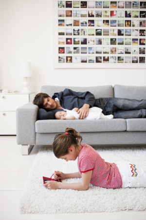 Girl playing while father resting