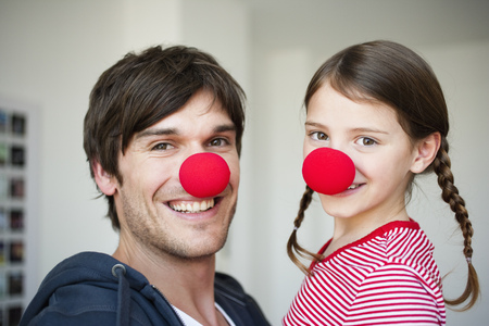 Father and girl wearing red noses