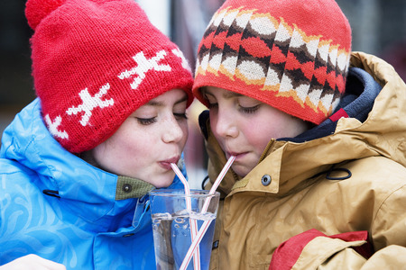 Two children drinking glass of water