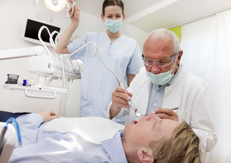 lays down: Dentist with patient in surgery LANG_EVOIMAGES