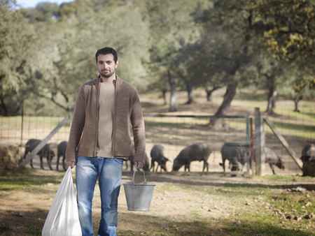 uncomplicated: Man on farm holding bucket and bag