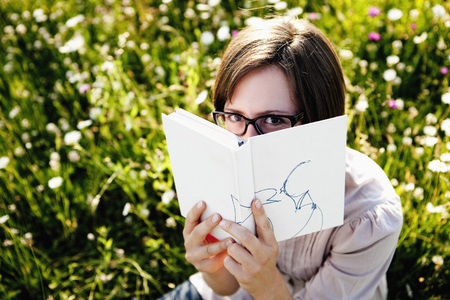 bashfulness: Woman hiding behind book