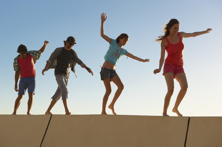 pursued: Young people balancing on wall