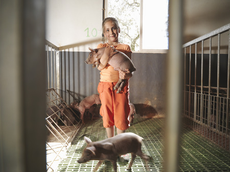 Child standing in pen holding a piglet