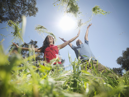 Couple throwing grass in the air