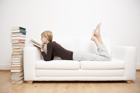 hushed: Woman reading a book on sofa