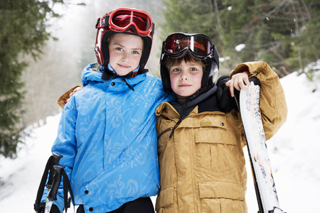 snows: Young children hugging in snow with skis