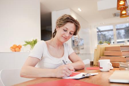 addressing: Woman writing address on an envelope