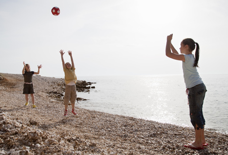 Children playing ball at the beach LANG_EVOIMAGES